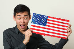 Young Asian student showing US national flag. And looking sideways Stock Photos