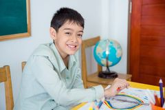 Young student sitting in classroom. Young asian student sitting in classroom and smiling at camera Stock Photo