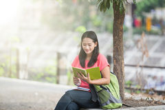 Young Asian student sitting outdoor, reading a book Royalty Free Stock Photography