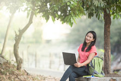 Young Asian student sitting outdoor, using a laptop Royalty Free Stock Photo