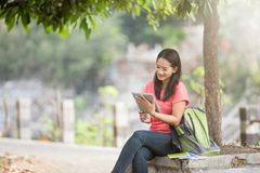 Young Asian student sitting outdoor, using a tablet pc Stock Photo