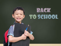 Young Asian student smiling in front of chalkboard Royalty Free Stock Photos