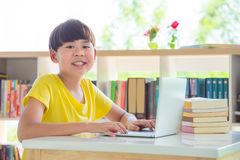 Student using laptop computer in library. Young asian student using laptop computer in school library Stock Image