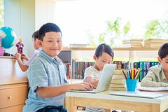 Student using laptop computer in library. Young asian student using laptop computer in school library Royalty Free Stock Images