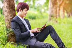 Young asian student working on tablet outdoors in park, or busin. Essman relaxing on grass Stock Image