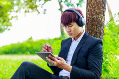 Young asian student working on tablet outdoors in park, educatio. N concept Royalty Free Stock Image
