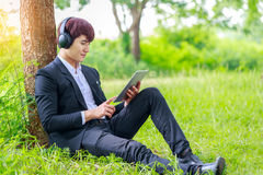 Young asian student working on tablet outdoors in park, educatio. N concept, or listening to music Stock Photos
