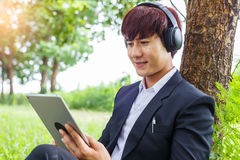 Young asian student working on tablet outdoors in park, educatio. N concept, or listening to music Royalty Free Stock Image
