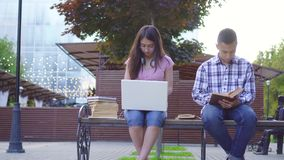 Young asian students man with a book and a woman with a laptop sitting on a bench stock footage