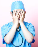 Young Asian surgeon wearing scrubs and looking stressed Royalty Free Stock Photos