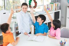 Young asian teacher ask question young kids in classroom . Young asian teacher ask question young kids in the classroom Royalty Free Stock Images