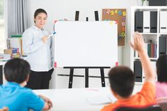 Young asian teacher ask question young kids in classroom . Young asian teacher ask question young kids in the classroom Stock Photography