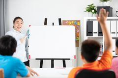 Young asian teacher ask question young kids in classroom . Young asian teacher ask question young kids in the classroom Stock Photo