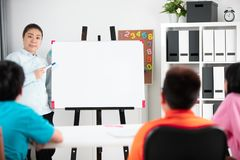 Young asian teacher ask question young kids in classroom . Young asian teacher ask question young kids in classroom with blabk white board Royalty Free Stock Photography