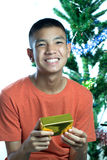 Young asian teen happy to get Christmas gift Royalty Free Stock Photos