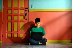 Young asian teen with a laptop computer in a living room Royalty Free Stock Images