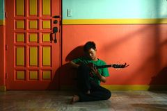 Free Young Asian Teen Playing The Guitar In A Living Room Stock Photos - 40032013