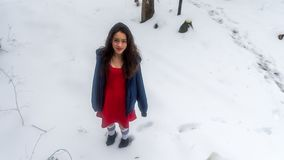 Young Asian teen in red dress surrounded by snow stock photo