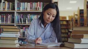 Young asian teenage girl is sitting at desk in big library rewriting text from book. She is tired and exhausted, looking. Young beautiful asian teenage girl is stock footage