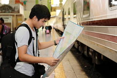 Young Asian tourist with a bag looking at map in train station . Royalty Free Stock Image