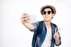 Young Asian tourist with hat smiling and holding smartphone taking a selfie photo isolated over white background. Young Asian tourist with hat smiling and royalty free stock photo