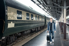 Young Asian tourist with luggage waiting train in station. Royalty Free Stock Images