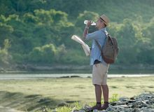Young Asian tourist man with backpack drinking water royalty free stock images