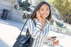 Young asian tourist on the phone and holding a city tour map Stock Photography