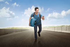 Young asian tourist running with holding phone and suitcase. On the road royalty free stock image