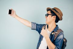 Young Asian tourist smiling and taking a selfie isolated over pastel blue background. Young Asian tourist smiling and taking a selfie isolated over pastel blue Royalty Free Stock Images