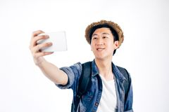 Young Asian tourist smiling and taking a selfie isolated over wh. Ite background Royalty Free Stock Images