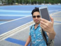 Young Asian tourist taking a photo or selfie. Selective focus and shallow depth of field.  royalty free stock photography