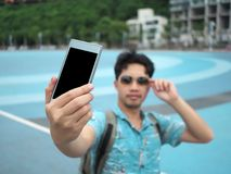 Young Asian tourist taking a photo or selfie. Selective focus and shallow depth of field.  stock photos