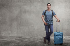 Young asian tourist on vacation with suitcase. On the city street Stock Photos