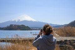 Young Asian tourists, aged 25-35, photographed with camera. Was photographed Mount Fuji. It is not a tourist destination in Japan. Young Asian tourists, aged 25 Royalty Free Stock Photo