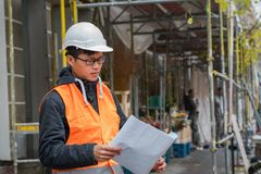 Young Asian trainee engineer at work on construction site. Young Asian apprentice engineer during his work on construction site. Outdoors royalty free stock photography