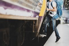 Young asian traveler with backpack in the railway, Traveler holding and stepping up to a train with backpack for journey travel at royalty free stock photos