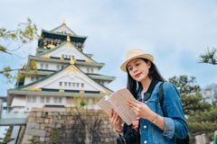 Young asian traveler holding guidebook visiting historical osaka castle with clear blue sky in the background. female tourist. Reading guide and finding the stock photography