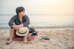 Young Asian traveler man sitting on the beach royalty free stock photography