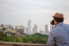 Young Asian traveler man wearing hat taking photo with dslr came stock image