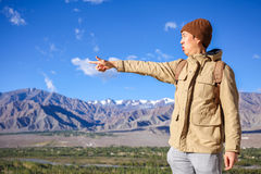 Young Asian traveler pointing out his finger for next destinations in high hill and blue sky background in Leh, Ladakh, India Stock Photo