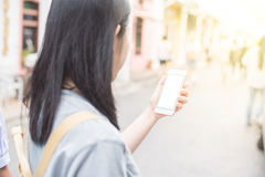 Young Asian traveling blogger or backpacker using route application on the mobile phone  to find the needed address in a city. Stock Photos