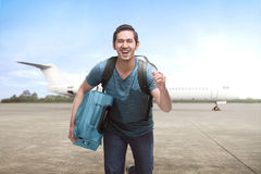 Young asian travelling man get off the plane with suitcase Stock Photo