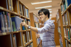 Young Asian university student in library. Young Asian man university student choosing book in library, education research and self learning in university life Stock Photography