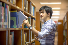 Young Asian university student in library. Young Asian man university student choosing book in library, education research and self learning in university life Royalty Free Stock Photo