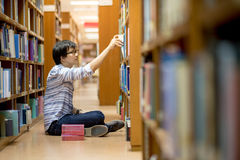 Young Asian university student in library. Young Asian man university student choosing book in library, education research and self learning in university life Royalty Free Stock Photos