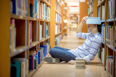 Young Asian university student in library. Young Asian man university student covering his head by book in library, education research and self learning in Stock Photo