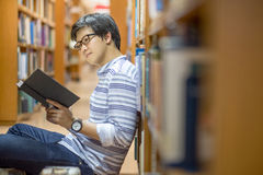 Young Asian university student in library. Young Asian man university student reading book in library, education research and self learning in university life Royalty Free Stock Photos