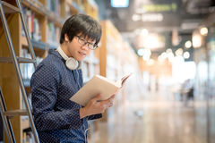 Young Asian university student in library. Young Asian man university student reading book in library, education research and self learning in university life Stock Photos