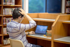 Young Asian university student in library. Young Asian man university student thinking about his project homework and using laptop computer in library, education Royalty Free Stock Image